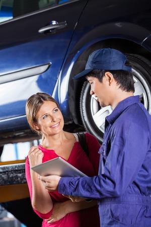 Felice cliente femminile guardando meccanico in possesso di tavoletta digitale in garage photo