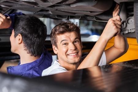 Ritratto di felice meccanico maschio che lavora sotto l'automobile sollevato con il collega al negozio di riparazione auto photo