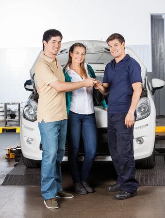 Ritratto integrale delle coppie dare le chiavi al tecnico, mentre in piedi davanti alla macchina a negozio di riparazione auto photo