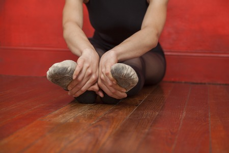 woman stretching: Low section of female ballet dancer stretching her legs in dance studio