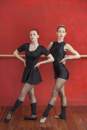 ballet studio: Full length portrait of young ballerinas practicing against red wall in dance studio Stock Photo