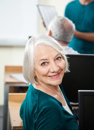 the elderly tutor: Portrait of happy senior woman at desk in computer class