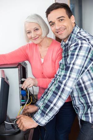 setup man: Portrait of happy teacher and senior woman fixing computer in classroom