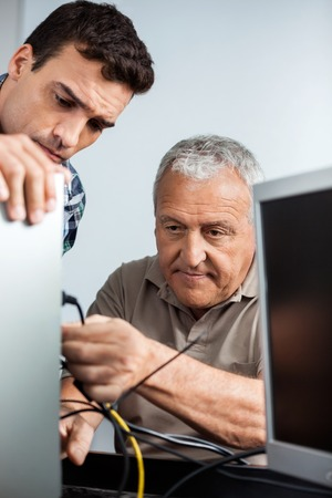 the elderly tutor: Male teacher watching senior man installing computer in class