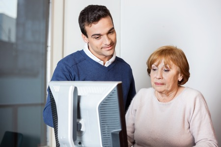 the elderly tutor: Young male teacher helping senior student at computer desk in classroom