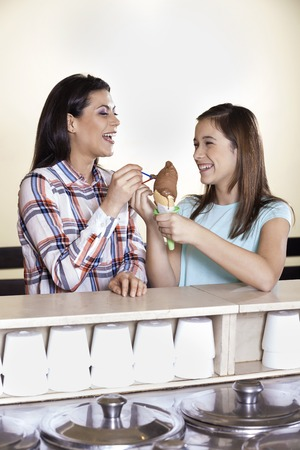 gelati: Happy mother and girl having chocolate ice cream at counter in parlor