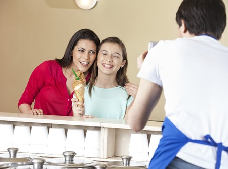 parlor: Waiter photographing happy mother and daughter with ice cream cone at parlor
