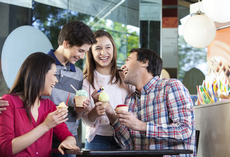 Family of four laughing while having ice creams at table in parlor Stockfoto