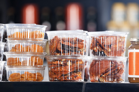Closeup of dry figs and red chili in takeaway containers at shop in supermarket