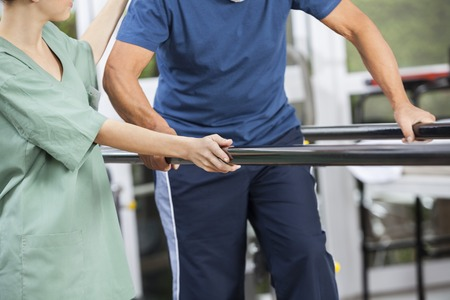 Midsection of female physiotherapist standing by senior man walking between parallel bars in fitness center