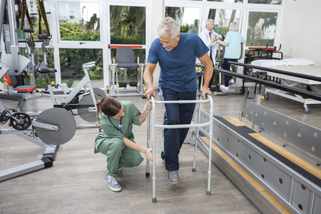 Hospital care: Young female nurse assisting senior man with walker in fitness studio of rehab center