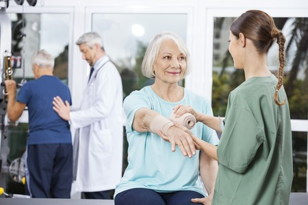 nursing staff: Smiling female patient looking at nurse putting crepe bandage on hand at fitness center