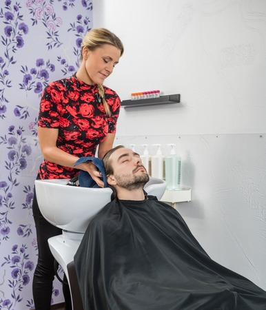 mid adult female: Mid adult female hairstylist drying male customers hair in salon