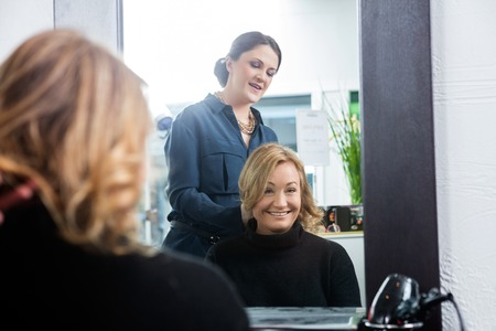 mid adult   female: Reflection of mid adult female hairdresser setting customers hair in salon Stock Photo
