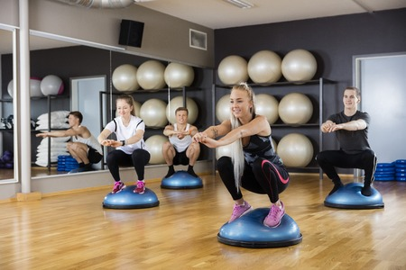 squatting: Male and female friends doing squatting exercise on bosu ball in gym