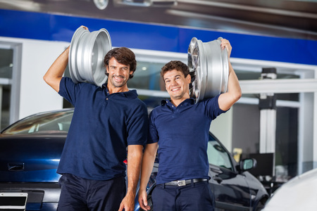 alloys: Portrait of happy technicians carrying metallic alloys on shoulders at auto repair shop