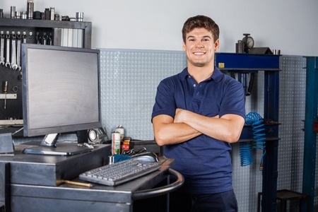 technician: Portrait of confident male technician standing arms crossed by computer in auto repair shop