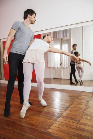 full length mirror: Full length of trainer practicing with ballerina in front of mirror at studio