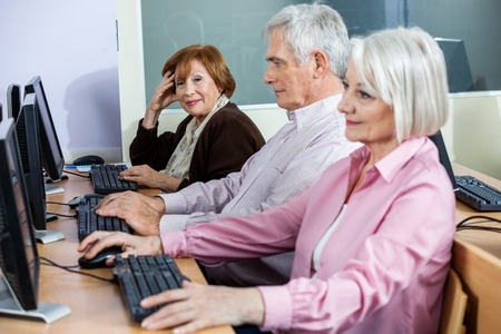 Portrait of smiling senior woman sitting in computer class with classmates studying at desk