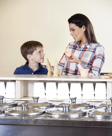 gelati: Smiling mother and son selecting between cones and cups at counter in ice cream parlor Stock Photo