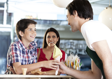 receiving: Happy boy receiving vanilla ice cream cone from waiter while standing by mother in parlor Stock Photo