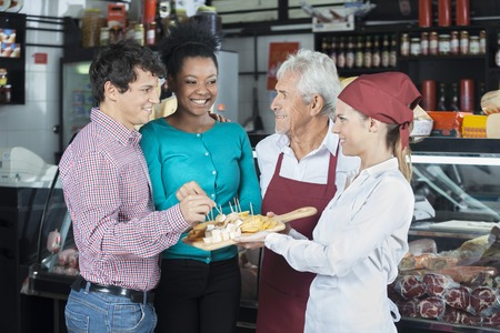 Happy salespeople offering free cheese samples to customers in shop Standard-Bild