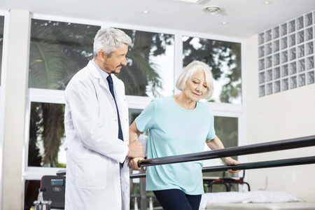 Mature male doctor looking at senior woman walking between parallel bars in fitness studio at rehab center Foto de archivo