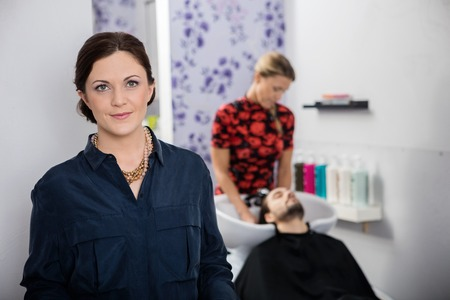 beauty parlour: Portrait of beautiful hairdresser with female associate washing customers hair in background