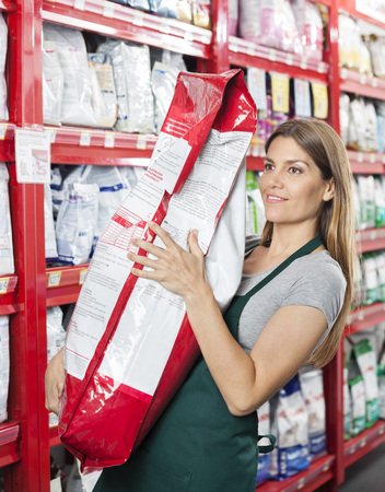 food package: Mid adult saleswoman carrying food package in pet store