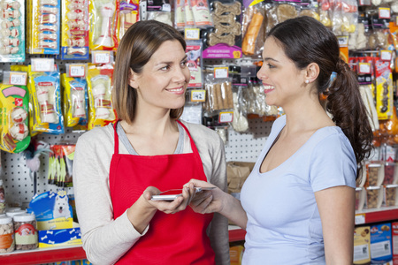 accepting: Smiling mid adult saleswoman accepting credit card payment from female customer in pet store Stock Photo