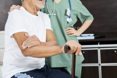 long term care services: Midsection of senior male patient with female nurse in rehab center Stock Photo