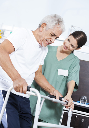 Young female nurse helping senior male patient in using walker at rehab center