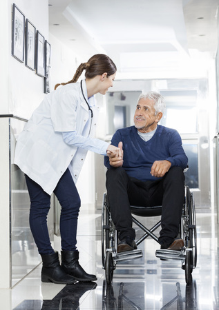 long term care services: Female doctor holding senior mans hand on wheelchair in rehab center