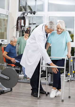 assisted: Senior woman using walker while assisted by male doctor at rehab fitness center Stock Photo