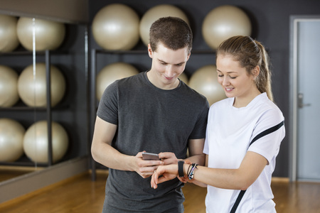 wearable: Smiling young male and female friends using cell phone and wearable in gym Stock Photo