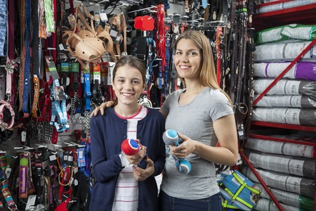 woman shop: Portrait of smiling mother and daughter holding toys for pet in store Stock Photo