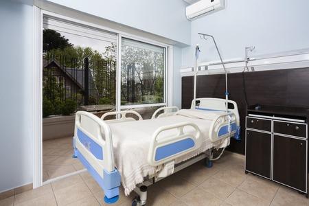 Modern bed by sliding door in rehabilitation center Foto de archivo