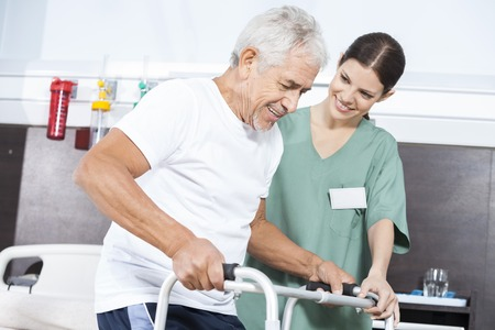long term care services: Smiling female nurse looking at happy senior patient using walker in rehab center