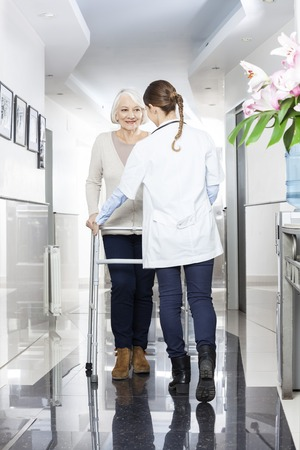 long term care services: Rear view of female doctor assisting senior patient with walker in rehabilitation center