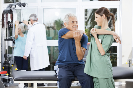 guiding: Smiling female nurse guiding senior man in stretching exercise at rehab fitness center