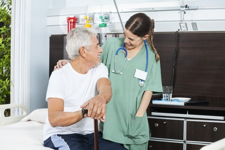 nursing young: Happy senior male patient and female nurse looking at each other in rehab center