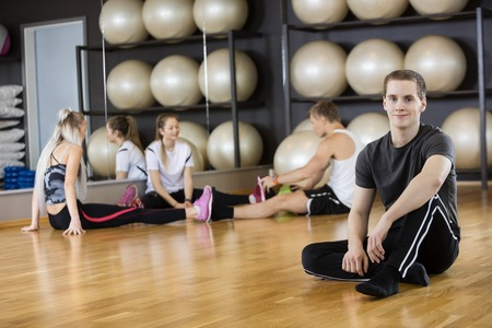 man sit: Full length portrait of confident man sitting on floor with friends in background at gym Stock Photo