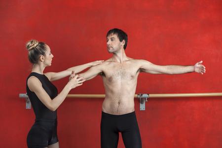 ballet hombres: entrenadora ayudar a bailarina de ballet masculino contra la pared roja en el estudio Foto de archivo