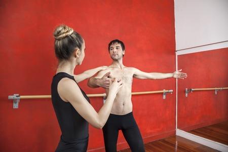 ballet hombres: entrenadora ayudar a bailarina de ballet masculino en el estudio de baile