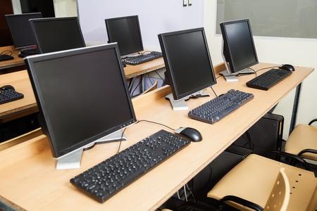 school classroom: Row of computers on desks in classroom