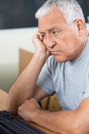 tensed: Tensed senior male student looking at computer while sitting in classroom