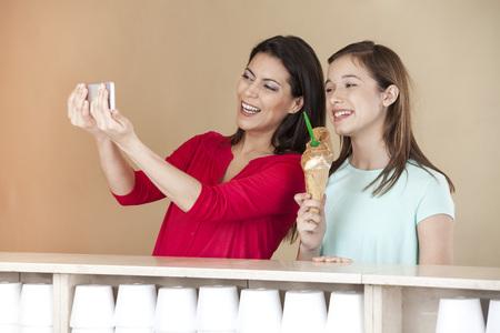 tomando refresco: Feliz mujer de mediana edad teniendo autorretrato con la hija que sostiene el helado de chocolate en el salón de Foto de archivo