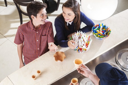 gelati: High angle view of happy siblings looking at each other at counter in icecream shop