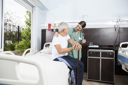 Senior male patient and young female nurse looking at each other in rehab center
