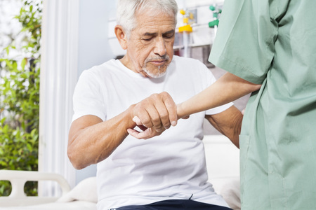 Disabled senior patient holding hand of female nurse in rehab center Standard-Bild